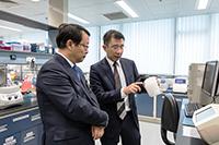 化學病理學系陳君賜教授(右)向黃衛副部長介紹華南腫瘤學國家重點實驗室﹙香港中文大學夥伴實驗室﹚概況