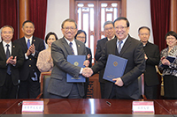 Professor Rocky Tuan (left) of CUHK signs collaboration agreements with Professor Hao Ping of PKU