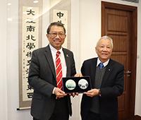 President Rocky Tuan (left) of CUHK presents a souvenir to Chancellor Ovid Tzeng of UST